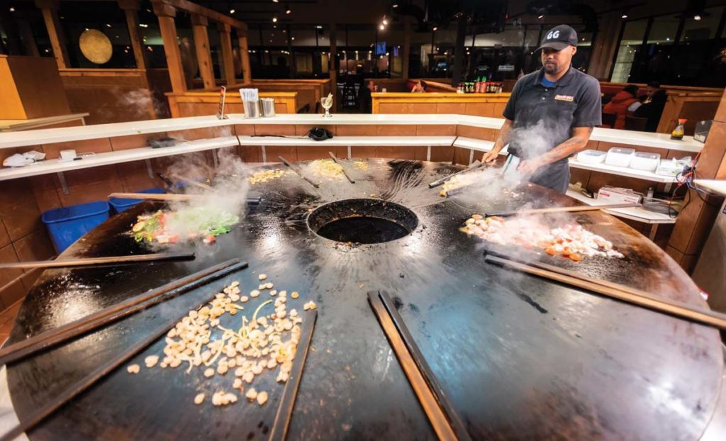 Sakieo Williams, a grill master at Genghis Grill, prepares stir fry. Meals at Genghis Grill are endless and completely customizable.